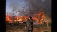 1968: inferno engulf home and surrounding area while firefighters work Stock Footage