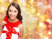 Smiling woman in red dress with christmas gift Stock Photos