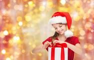 Smiling girl in santa hat with christmas gift Stock Photos