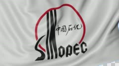 Close up of waving flag with Sinopec logo, seamless loop, blue background Stock Footage