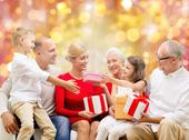 Happy family with christmas gifts over lights Stock Photos