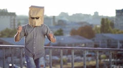 Man with paper bag over head dancing Stock Footage