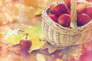 Close up of basket with apples on wooden table Stock Photos