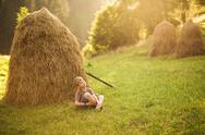 Kid sitting alone on green grass in scenic place near dry hay Stock Photos