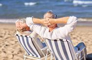 Senior couple sitting on chairs at summer beach Stock Photos