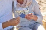 Happy senior couple drinking wine on summer beach Stock Photos
