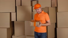 Delivery man in orange uniform delivering damaged parcel to customer. Brown Stock Footage