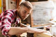 Carpenter working with wood plank at workshop Stock Photos