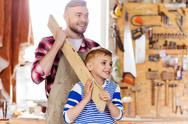 Happy father and son with wood plank at workshop Stock Photos