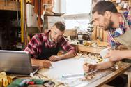 Carpenters with laptop and blueprint at workshop Stock Photos