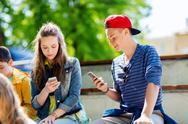 Happy teenage friends with smartphones outdoors Stock Photos