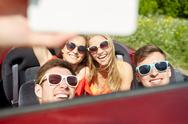 Friends driving in cabriolet car and taking selfie Stock Photos