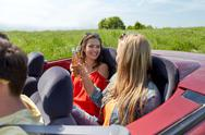 Happy friends driving in cabriolet car with beer Stock Photos