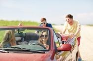 Happy friends pushing broken cabriolet car Stock Photos