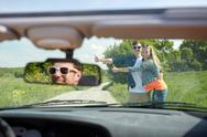 Couple hitchhiking and stopping car on countryside Stock Photos