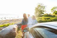 Happy teenage girls or women near car at seaside Stock Photos