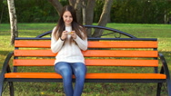 Footage young woman uses the app on your smartphone in the park. 4k Stock Footage