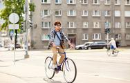 Young hipster man with bag riding fixed gear bike Stock Photos
