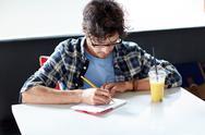 Man with notebook and juice writing at cafe Stock Photos