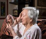 Old woman looking into a mirror Stock Photos