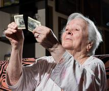 Woman looking at torn one hundred dollar bill Stock Photos