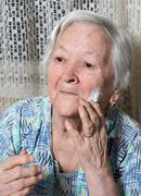 Old woman applying anti-aging cream Stock Photos