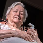 Old sick woman with asthma inhaler Stock Photos