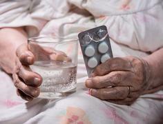 Old sad woman holding pills Stock Photos