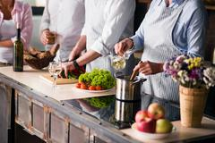 Family and friends cooking food at dinner table Stock Photos