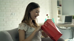 Happy woman checking shopping bag sitting on sofa at home Stock Footage
