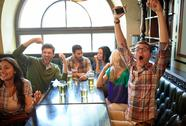 Friends with beer watching football at bar or pub Stock Photos