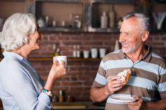 Man and woman in their sixties telling jokes in kitchen Stock Photos