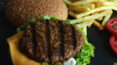 Beef hamburger grill french fries pickled cucumber tomato cheese food dish Stock Footage