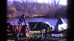 1962: two men working outdoors with a tractor near boats on the water's edge Stock Footage