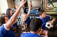 Fans or friends watching football at sport bar Stock Photos