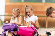 Group of happy elementary school students outdoors Stock Photos