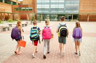 Group of happy elementary school students walking Stock Photos