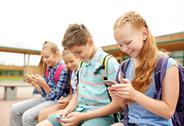 Elementary school students with smartphones Stock Photos