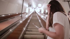 Pretty girl in subway. Brunette young woman in a white T-shirt on an escalator Stock Footage