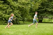 Happy kids running and playing game outdoors Stock Photos