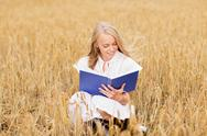 Smiling young woman reading book on cereal field Stock Photos