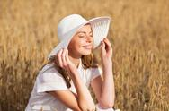 Happy young woman in sun hat on cereal field Stock Photos