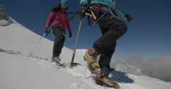 Two Female Mountaineers Descending Snowy High Altitude Mountain Stock Footage