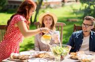 Happy friends having dinner at summer garden party Stock Photos
