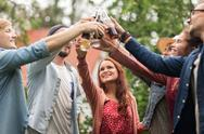 Happy friends clinking glasses at summer garden Stock Photos