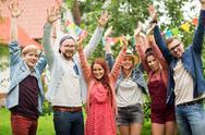Happy teen friends waving hands at summer garden Stock Photos
