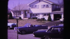 1962: a couple in a convertible pulling out of the driveway and driving down  Stock Footage