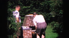 1962: a father and son outdoors grilling on the brick bbq pit HAGERSTOWN Stock Footage
