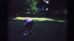 1962: children ignite a firecracker under a bucket and play on a swing set  Stock Footage