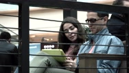 Pretty brunette girl and man in black rim glasses using tablet pc together in a Stock Footage